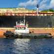 Tugboat guiding a huge cargo ship - Stockfoto