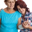 Elderly woman with a broken arm and her caregiver - Stock Photo
