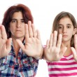 Latin women signaling to stop with their hands - Stock Photo