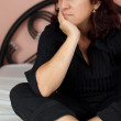 Woman sitting in her bed with a worried expression — Stock Photo #19582357