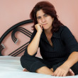 Beautiful hispanic woman sitting in her bed — Stok fotoğraf