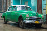 Shabby rusty Plymouth under the rain in Old Havana — Stock Photo