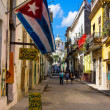 Stock Photo: Typical street in Old Havana with a big cuban flag
