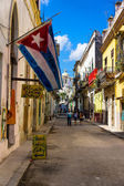 Typical street in Old Havana with a big cuban flag — Stok fotoğraf