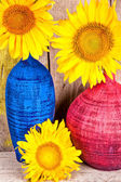 Bright yellow sunflowers on colorful vases — Stock Photo