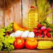 Fresh vegetables, eggs and bottle of oil on basket — Stock Photo #22174837