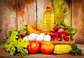 Fresh vegetables, eggs and a bottle of oil on a basket — Stock Photo
