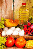 Assorted vegetables , eggs and a bottle of oil on a basket — Stock Photo