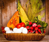 Assorted vegetables and eggs on a basket — Stock Photo