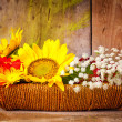 Flowers on a basket with a rustic wooden background — Stock Photo