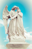 Statue of an angel guarding a beautiful young girl — Stock Photo
