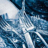 Blue toned image of forks and knives washed on a sink — 图库照片