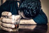 Drrunk homme tenant un verre et dormir sur une table — Photo