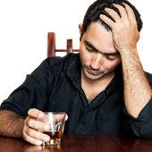 Hombre hispano sosteniendo una bebida alcohólica y sufriendo un dolor de cabeza — Foto de Stock