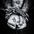 Two hands locked with a chain on a black background — Stock Photo
