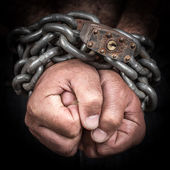 Two hands chained with an iron chain and a padlock — Stock Photo