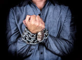 Hands of a formally dressed man chained together — Stock Photo
