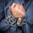 Hands of a formally dressed man chained with an iron chain and a — Stock Photo