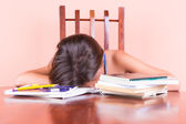 Exhausted student sleeping with her head on a table — Stock Photo