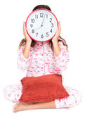 Child in pajamas wearing a clock in place of her face — Stock Photo