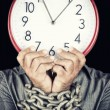 Man holding a clock in place of his face with his hands chained — Stock Photo #26724915