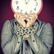 Man holding a clock in place of his face with his hands chained — Stock Photo