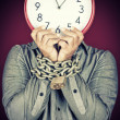 Man holding a clock in place of his face with his hands chained — Stock Photo #26724949
