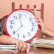 Tired child sleeping and holding a clock — Stockfoto
