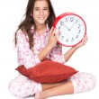 Girl wearing pajamas and holding a clock — Stock Photo