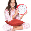 Stock Photo: Girl wearing pajamas and holding clock
