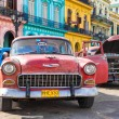 Old Chevrolet near colorful buildings in Havana — Stock Photo