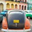 Old car parked near colorful buildings in Havana — Stok fotoğraf
