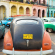 Stock Photo: old car parked near colorful buildings in havana