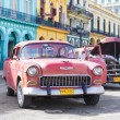 Old Chevy next to colorful buildings in Havana — Stock Photo