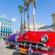 Red chevrolet and other vintage cars in Havana — Stok fotoğraf