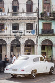 Old car next to crumbling buildings in Havana — Stock Photo