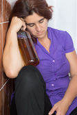 Drunk latin woman sleeping in the bathroom with a bottle of liqu — Stock Photo