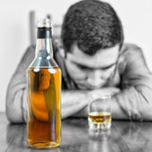 Whisky bottle with an out of focus drunk man — Stockfoto