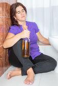 Drunk latin woman sitting on the toilet floor holding a bottle — Stock Photo