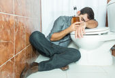 Drunk hispanic man sleeping over the toilet bowl — Stock Photo