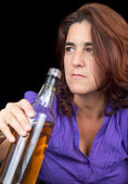 Drunk latin woman holding a whsky bottle — Stock Photo