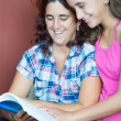 Hispanic mother and her daughter reading a book — Stock Photo
