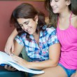 Hispanic mother and her pretty daughter reading — Stock Photo