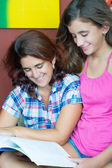 Latin mother and her daughter reading a boo — Stock Photo