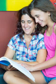 Hispanic mother and her daughter reading a book — Stok fotoğraf