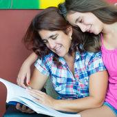 Madre di latino e sua figlia adolescente leggendo un libro — Foto Stock