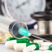 Syringe, different pills, stethoscope and sphygmomanometer — Stock Photo