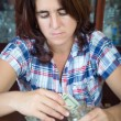 Worried  hispanic woman counting her savings at home — Stock Photo