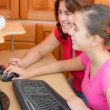 Stock Photo: Happy latin girl and her young mother working on computer