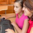 Hispanic girl and her mother working on a computer — Stock Photo #32017527